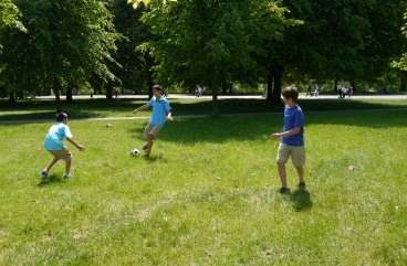 Aidan, Nathan, and Anders playing football in Hyde Park.