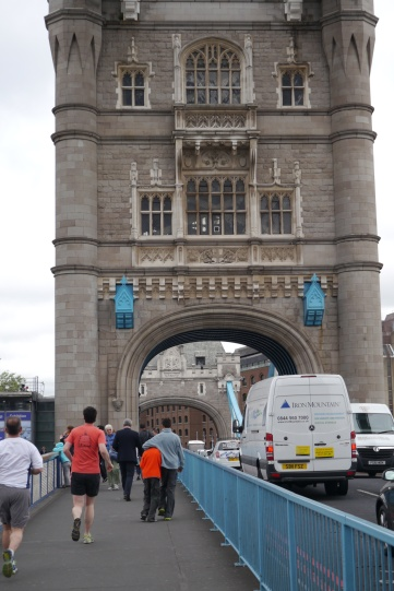 The boys are walking across the Tower Bridge. What looks like a hug... is really a headlock. Brothers.