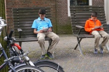 Boys read about the Anne Frank House while we wait in the one-hour long line.