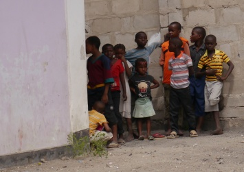 Center and neighborhood children watch performance.