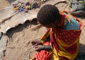 One of the village girls making jewelry