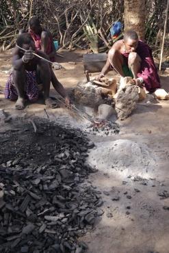 Datoga men melt metal over fire for bracelets.