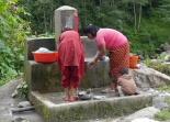 Women wash dishes at community faucet. The little boy is helping too.