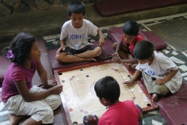 Kids playing board game, Bagh Chal.