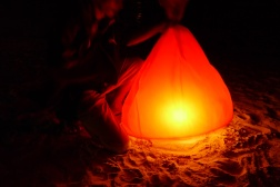 Vendor named Em lights the red lantern.