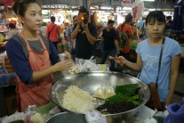Vendor makes mango sticky rice.