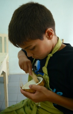 Aidan shreds the inside of a coconut with a really nifty tool.