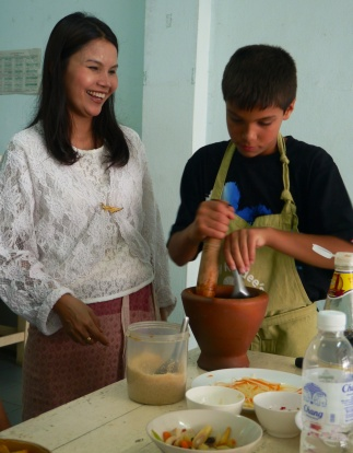 Dion teaches Aidan the secret to using a mortar and pestle.