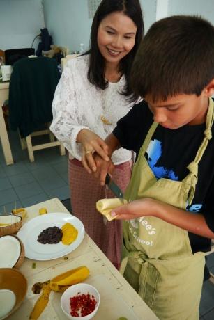 Aidan cuts banana from sticky rice dessert.