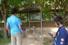 Nathan and Aidan listen to the audio tour explain about this mass gravesite, one of many unearthed at the Killing Fields.