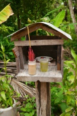 Villagers offer gifts to their dead ancestors at their spirit houses.