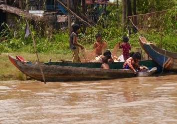 These children look to be collecting trash in a fishing net.