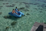 Boys pedaling through crystal clear water