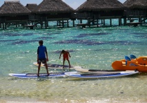 Boys play leap frog on paddle boards. No water sports this morning because of strong wind and current.