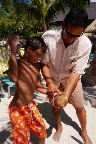Aidan cracks the coconut with a stone. He drinks all the water for himself!