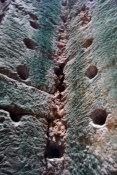 These holes were made by people looking for gems inside the walls of the temple.