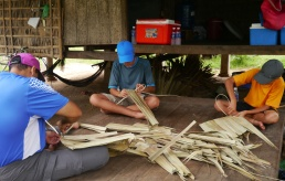 Nathan, Neerav, and Aidan work to connect the palm leaves that will be used to construct kitchen walls. The owner needs 300 panels!