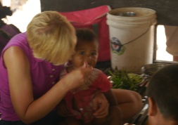 The little boy finally sits on Shellie's lap. Her secret weapon: food.